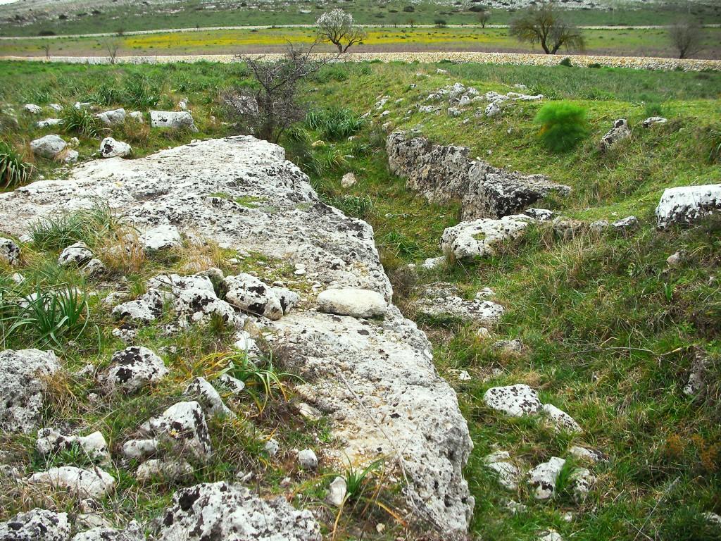 Murgia Timone - Due ellissi segnano il perimetro visibile del grande insediamento Neolitico, Solo un duro lavoro e la cooperazione collettiva, usando solo strumenti di pietra, ha reso possibile lo scavo