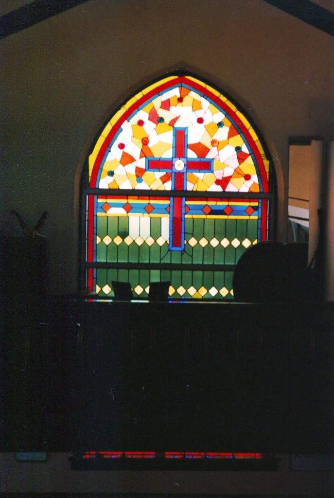Particolare della vetrata originale con la croce cristiana